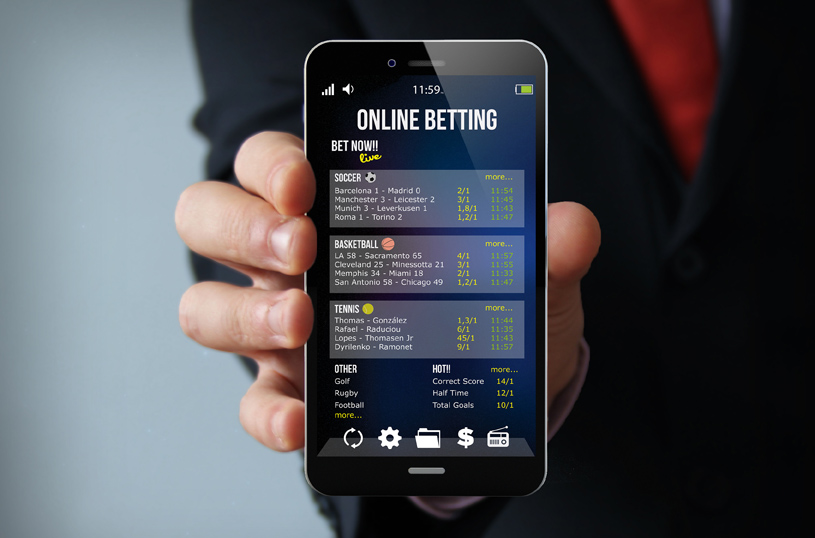 gambling concept: businessman hand holding a touch phone with bet app